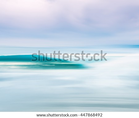 A breaking ocean wave with a moody sky. Image made with a long exposure for a soft blurring effect. - stock photo