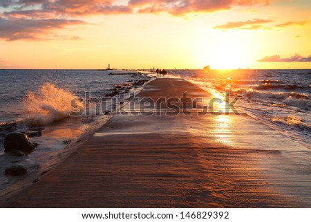 A breakwater walkway at sunset - stock photo