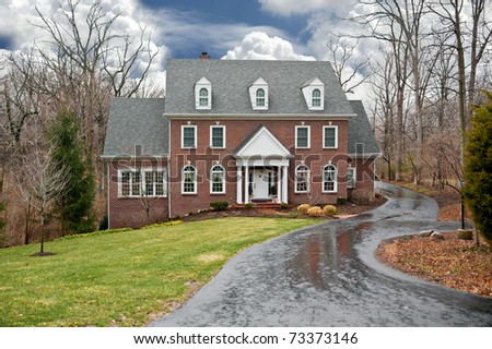 A brick two-story house in a secluded wooded setting with an asphalt driveway on a wet, rainy winter day. - stock photo