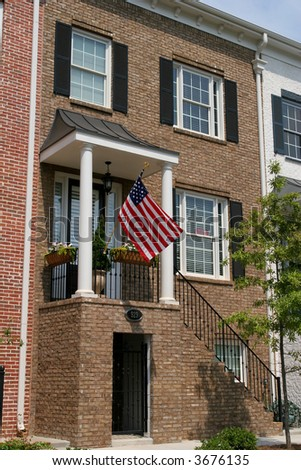 A brick two story townhouse with an American flag out front - stock photo