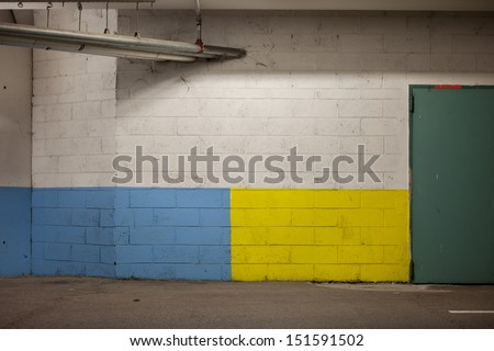 A brick wall colored.  Blue and yellow on the bottom, white on the top. Suspended metal pipes and half door. - stock photo
