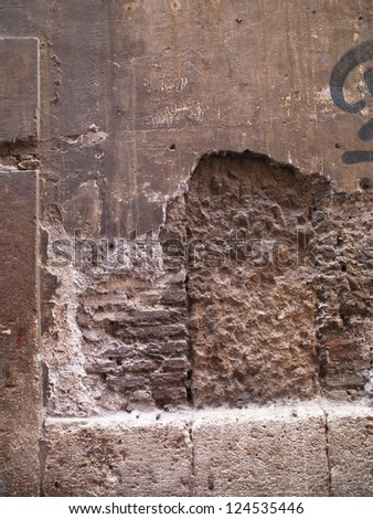 A brick wall formerly covered with plaster or cement now exposed - stock photo