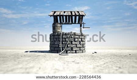 A brick water well with a wooden roof and bucket attached to a rope in a flat barren landscape with a blue sky background - stock photo