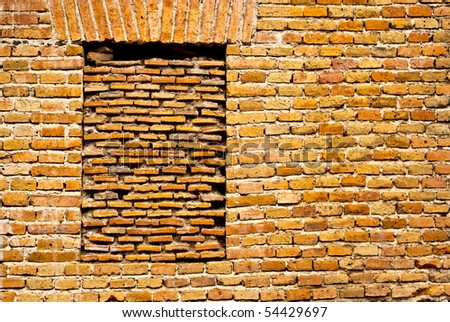 A bricked window in a brick wall creates a contrast in patterns - stock photo