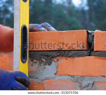 A bricklayer using a level to check his wall - stock photo