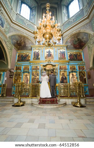 A bride and a groom are standing in the Orthodox church at wedding ceremony