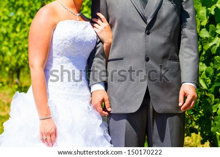 A bride and groom are close together showing just their torso arms and hands while holding each other after their wedding. - stock photo