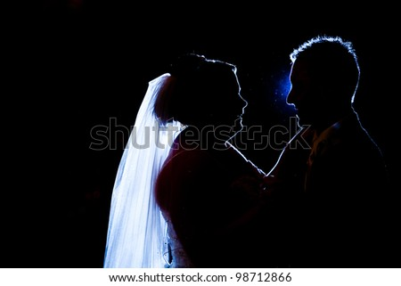 A bride and groom are having their first dance. silhouette of a couple dancing - stock photo