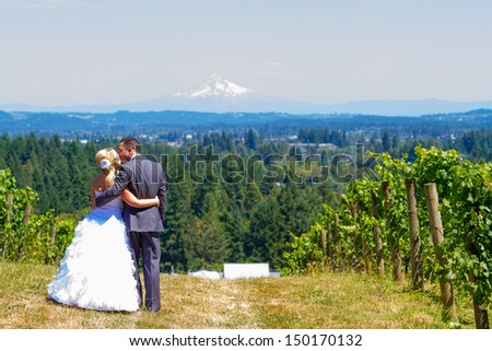 A bride and groom enjoy a view of mount hood in the background from this high elevation winery vineyard in Oregon just outside of Portland. - stock photo