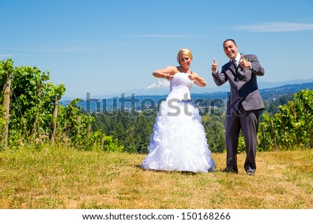 A bride and groom give a bigs thumbs up to the camera on their wedding day. - stock photo