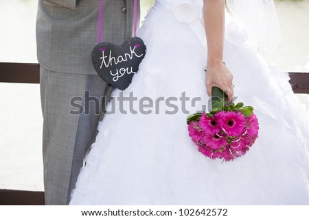 A bride and groom holding a heart shaped thank-you sign. - stock photo