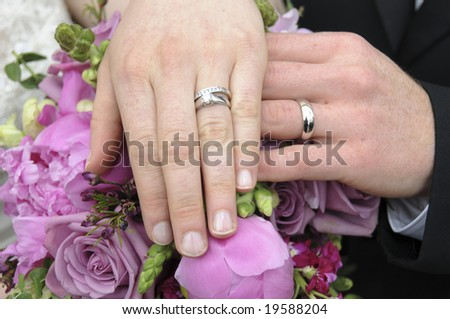 A bride and groom show off their wedding rings by placing their left hands on the bride's bouquet - stock photo
