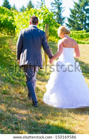 A bride and groom walk away from the camera after their ceremony at a vineyard winery in Oregon. - stock photo