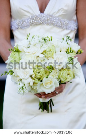 a bride holding a green and white wedding bouquet of flowers - stock photo