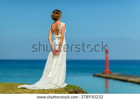A bride in a white dress is staring at the ocean and a pier - stock photo