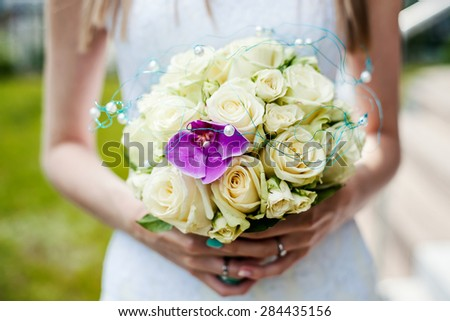 A bride is holding her bridal bouquet.