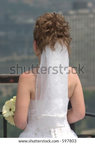 A bride looking off into the distance. - stock photo