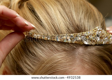 A bride putting her tiara on her head - stock photo