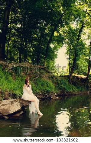 A bride sitting on a rock on a riverbank