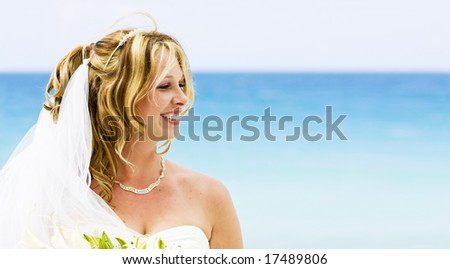 A bride smiling on the beach - stock photo