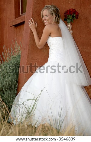 A bride standing against a building - stock photo