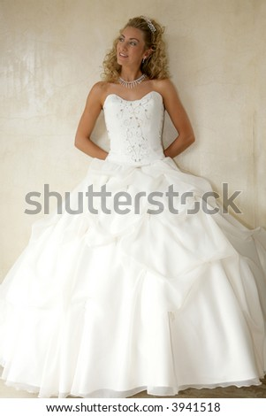 A bride standing against a wall in her gown - stock photo