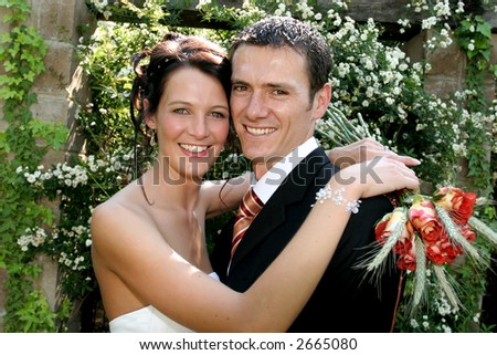 A bride standing with her arms around groom