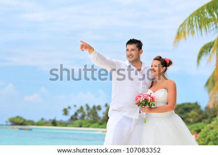 A bride with a bouquet of flowers and groom looking towards, shot on a beach in Kuredu resort, Maldives island, Lhaviyani atoll - stock photo