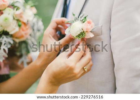 a brides hand putting the boutonniere flower on a groom  - stock photo