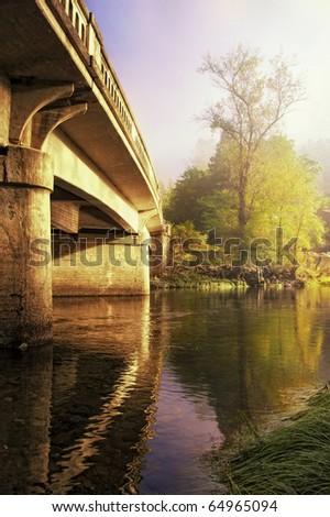 A Bridge lit by sunlight in a foggy morning near Yosemite National Park - stock photo