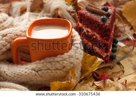 A bright and cozy autumn composition with an orange cup of milk tea, a beige knitted scarf, a piece of appetizing cake with blueberries, dry tree leaves, hips, chestnuts and cinnamon sticks