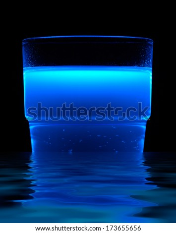 a bright blue fluorescent illuminated drink and reflective water surface in black back - stock photo