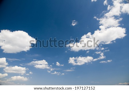 A bright blue sky with clouds in it. - stock photo