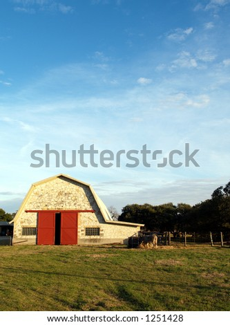 A bright blue Texas sky over a barn with red doors.