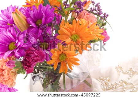 A bright cheery flower arrangement filled with pink and orange flowers on a white background with copy space, horizontal with selective focus, great for Mother's Day - stock photo