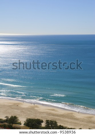 a bright clear blue sky day aerial photo over ocean beach, beautiful day, beautiful beach at Surfer's Paradise, Queensland, Australia