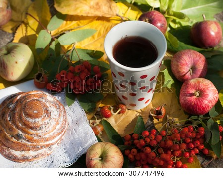 A bright composition with a cup of strong black tea, a sweet bun with raisins, ash berries, apples and colorful autumn leaves on a stone surface    - stock photo