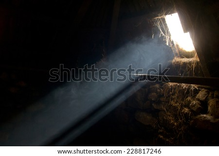A bright light beam enters an old hay barn