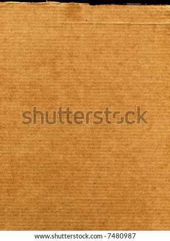 A bright piece of torn cardboard for uses as a background - stock photo