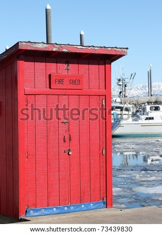 "A bright red building labeled ""Fire Shed"" in the harbor with icy water and boats in the background"