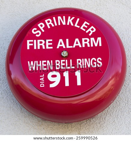 A bright red fire alarm bell on a wall - stock photo