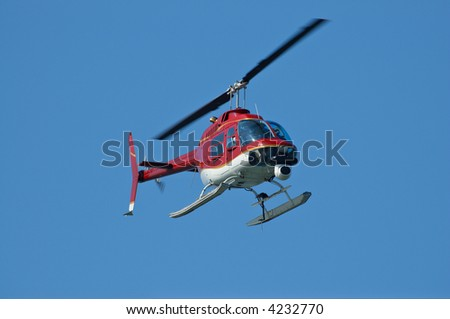 A bright red helicopter with a camera. A little motion blur on rotor blades - stock photo