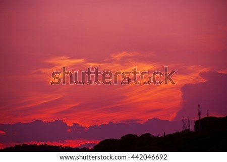 A bright red sky at night with trees below