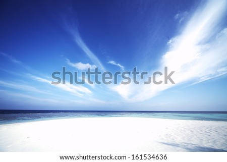 A bright white sandy beach on a sunny day. - stock photo