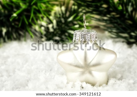 A bright white star in the snow with fir branch in the background - stock photo