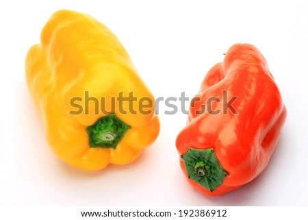 A bright yellow and a bright red pepper - stock photo