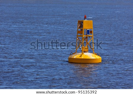 A bright yellow buoy floating in the St. Laurence Seaway, near Quebec City. - stock photo