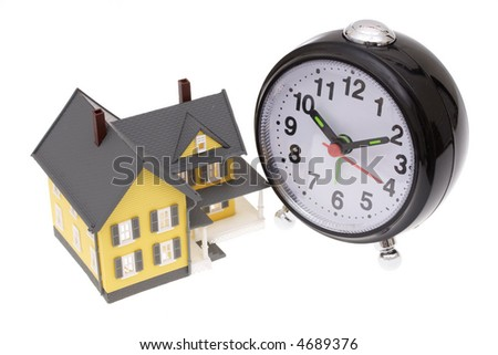 A bright yellow house with an alarm clock - stock photo