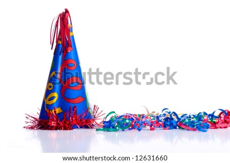 A brightly colored birthday hat and streamers on a white background with copy space - stock photo