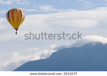 A brightly-colored hot air balloon floats in the blue New Mexico sky with cloud-covered Sandia Mountains in the background - horizontal orientation - stock photo